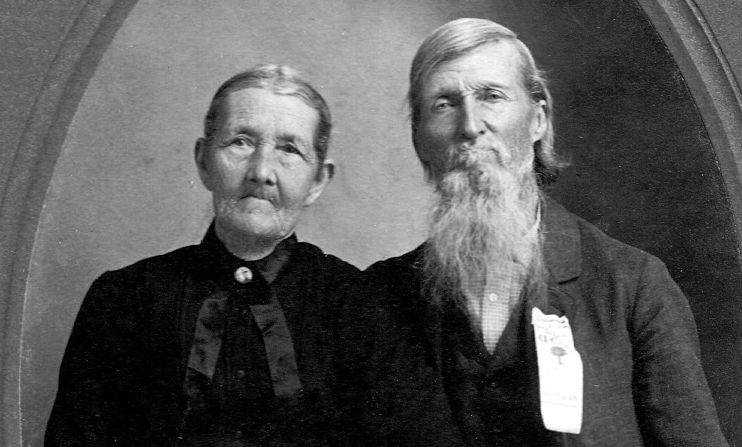 B&W photo of elderly couple in Sunday clothes. Woman with hair pulled back and wearing black blouse. Man with longish hair and a long white or grey beard. Wearing a white button down shirt and a dark jacket over it. He is also wearing an award of some kind pinned to her jacket, perhaps something from his service during the Civil War.