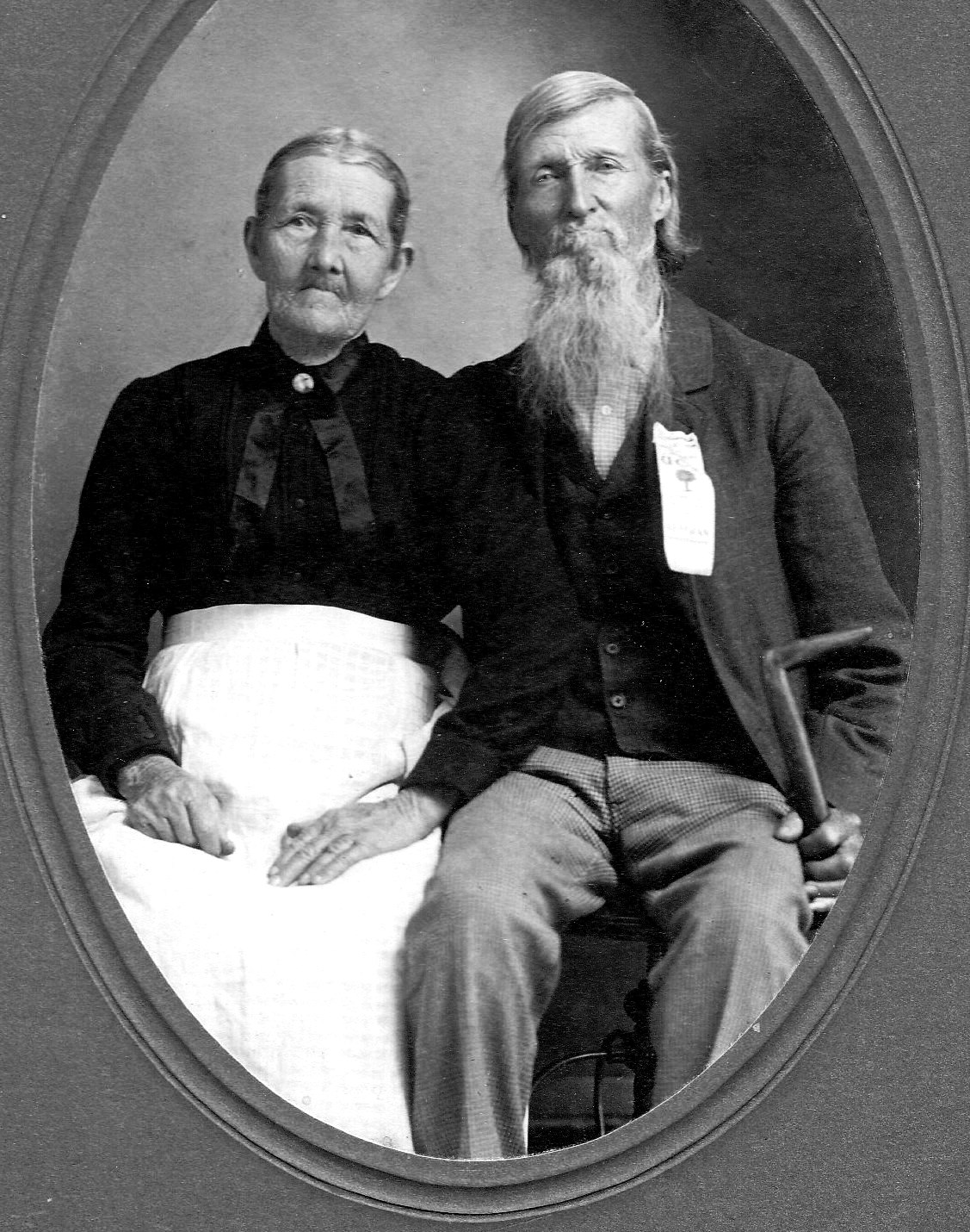 B&W photo of elderly couple in best clothes. Woman wearing black blouse, white skirt. Hair pulled back. Man wearing vest and jacket. Hair combed and long beard tidy. He's holding a cane because of leg injury in Civil War.