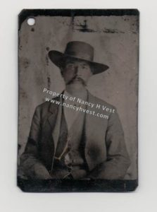 tintype of a man in a dark suit with a vest and white shirt wearing a dark hat. He has a dark mustache. Not smiling.