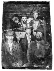 group tintype of 6 men in a building of some kind. Each man wearing a hat and a coat. Some seated. Some standing.