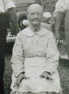 B&W photo of an elderly woman sitting down. She's wearing a light patterned long sleeve dress and a white apron at her waist. He white hair is pulled back.