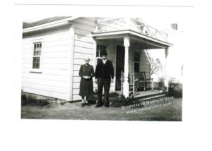 Elderly couple, both wearing dark clothes, standing in front of a small white house with a small porch.