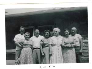 B&W photo of 7 smiling people in front of house. All are middle-aged except for one who is elderly. Clearly a warm day since everyone is in short sleeves.