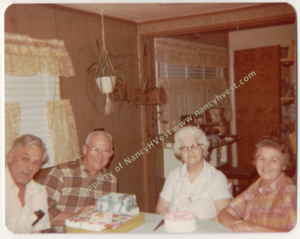 Four people seated at a table with presents and a cake on the table. From left: gray haired, ruddy-faced man wearing an off-white button shirt; balding white haired man with glasses wearing a brown and beige checkered shirt; white-haired elderly woman with dark glasses and wearing a white dress; brown-haired woman wearing a red and beige checkered dress. All smiling.