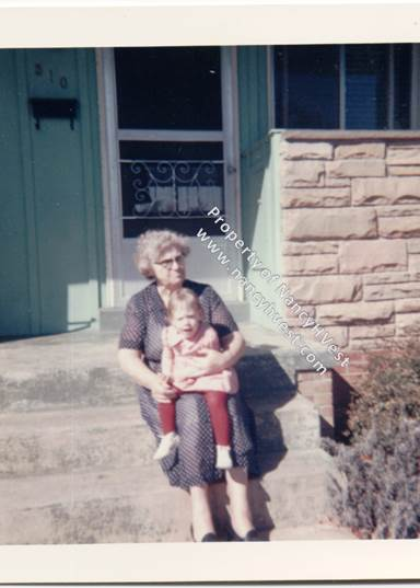 Color photo of an elderly woman sitting on porch steps with an approximately 18 month old girl in her lap. Woman is wearing a short-sleeved, dark, swiss-dotted. Hair is graying and she's wearing dark-rimmed glasses. Blonde-haired girl is wearing a red and white dress, red tights, and white shoes.
