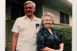 Color photo of smiling couple in front of a green house. Man is wearing a white polo and has gray hair. Woman is gray-haired and wearing a black shirt with green and purple color pattern it.