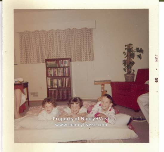 Color photo of 3 children laying in the floor on sleeping bags and pillows. All are smiling. Girl on left is about 4, middle girl is about 13, and boy on the right is about 10.