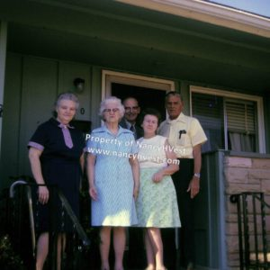 Color photo of 5 people standing on a porch. Everyone in short sleeves. Woman on the left has graying hair and a cane nearby. Next woman has write hair, dark glasses, and wearing a blue dress. Woman in middle has dark hair and wears a green skirt with a cream colored top. Man in middle in a grey suit. Man on right wearing a yellow shirt and dark pants.