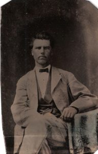tintype of a man about 30-40 wearing a light colored suit with a darker vest and a black bowtie. He is seated and his left leg crossed over the right and his left arm resting on a table. Dark hair, clean-shaven.