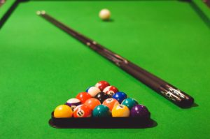 Color photo of a pool table with balls in a rack, 2 pool cues and an eight ball.