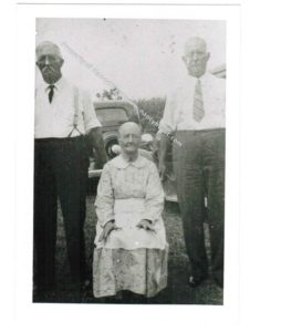 B&W of 3 elderly people, 2 men standing and woman sitting. Men wearing white shirts, dark pants and ties. Man on left has white hair. Man on right is nearly bald. Woman wearing a light colored collared dress and a white apron. There is a car in the background.