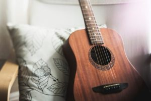 Color photo of a brown acoustic guitar leaning against the back of a chair cushion that is white with a leaf drawing on it.
