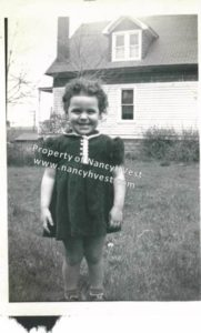 B&W of a girl about 4 years old. Dark, curly hair. Dark short sleeve dress. Smiling widely.