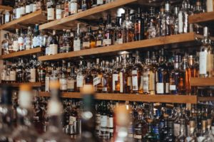 Color photo of wooden shelves with hundreds of whiskey bottles on them