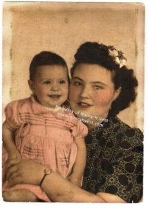 Colorized photo of a young woman with mid-neck length dark wavy hair with a flower in her hair. She is wearing a black and white dress. She is holding a girl about 2 years old wearing a pink short sleeved dress. Girl and very short dark hair. Both are smiling.