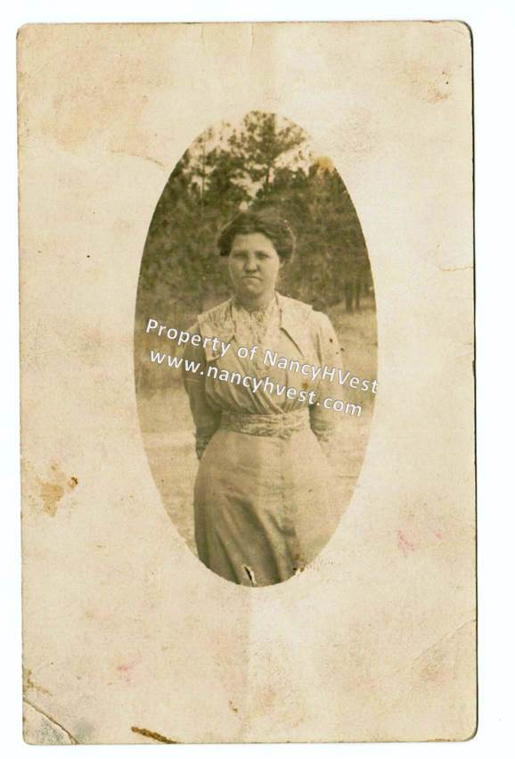 B&W photo of a young female teacher in a white dress with dark hair pulled back and up.. Not smiling.