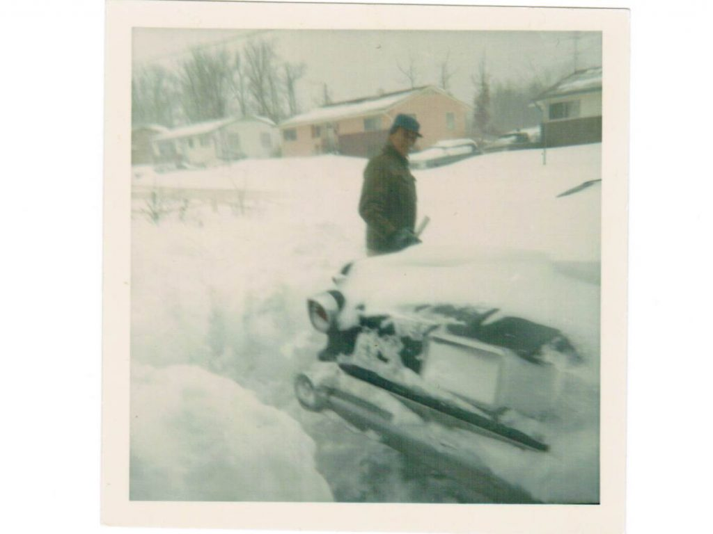 Color photo of a man shoveling snow from around an early 1960's car. Houses can be seen in the background.