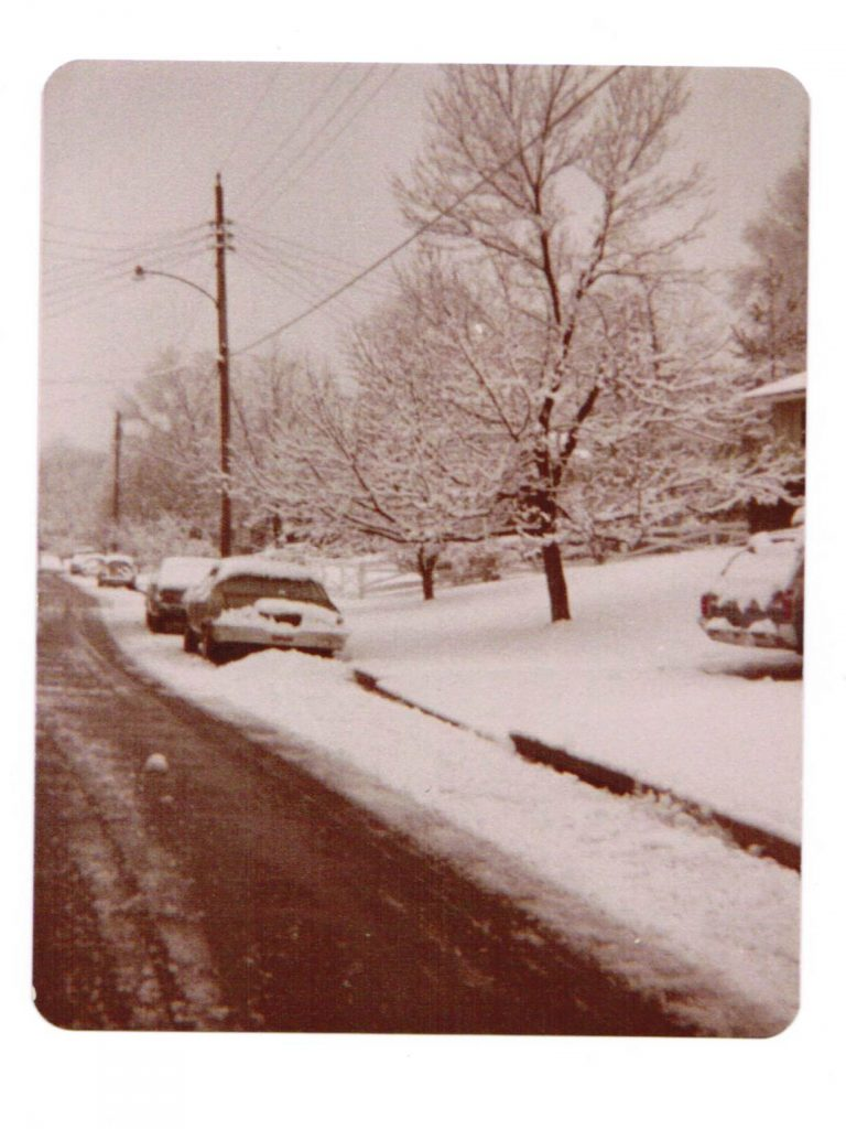 Faded color photo of snow on a suburban street with a car in a driveway and several cars on the street. A street light is visible.