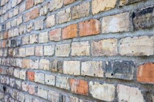 Color photo of a brick wall with white, burnt orange and grey bricks.