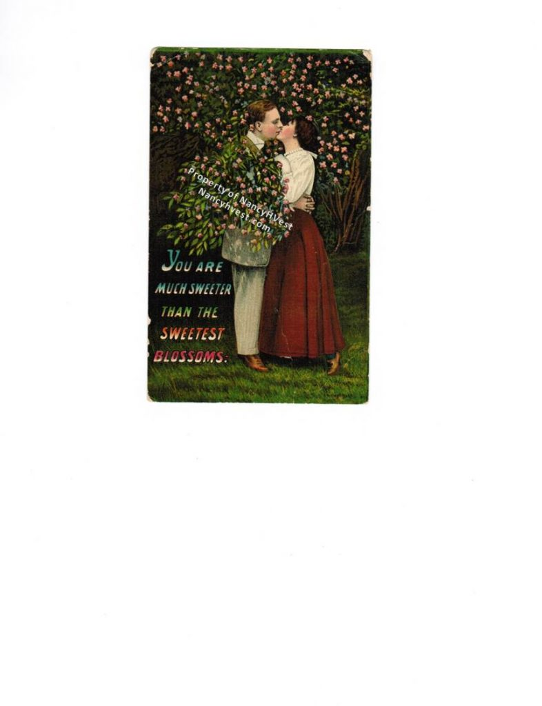 A post card from in color showing the man kissing a woman in front of a flowering tree. Man in a suit. Woman is a long red skirt and white blouse.