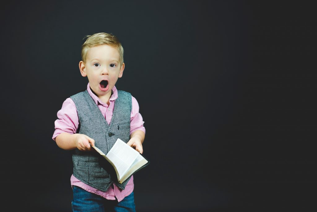 Color photo of young blonde boy in a gray vest, pink shirt, and blue pants holding a book. He has mouth open wide like he's surprised.