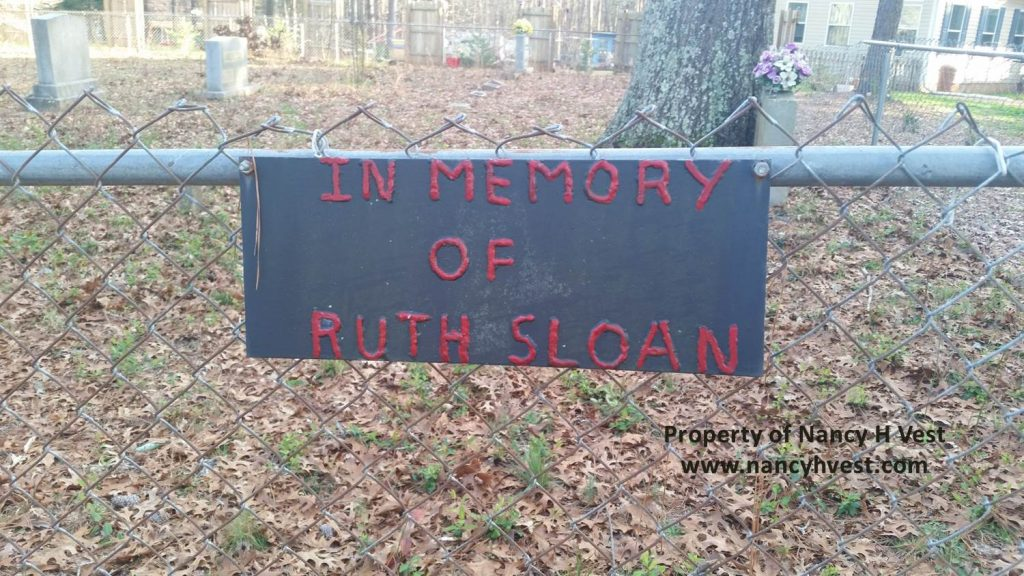"Color photo of sign. Sign is dark gray and made of metal. Red lettering says ""In memory of Ruth Sloan"""