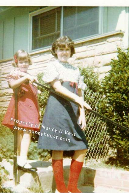 Color photo of 2 girls standing on steps in front of a green and brick house. Younger girl in a red dress. Older girl in a blue dress.