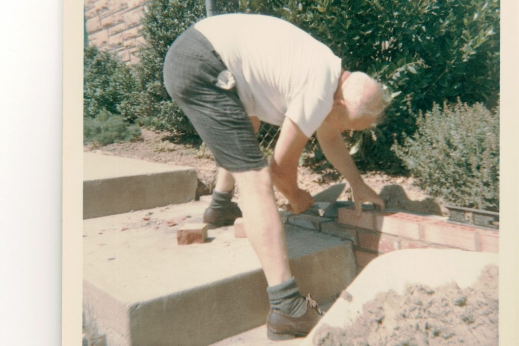 Color photo of a balding man in a white shirt, dark gray shorts and socks, and brown shoes; bending over while laying bricks.