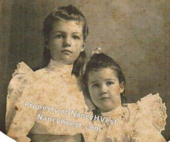 B&W photo of two girls with dark hair in white blouses, one girl clearly older than the other.  circa 1908