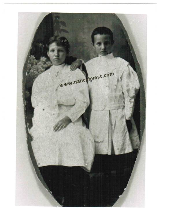 B&W of two girls with dark hair in white dresses, one seated and one standing. One standing has short hair. circa 1910