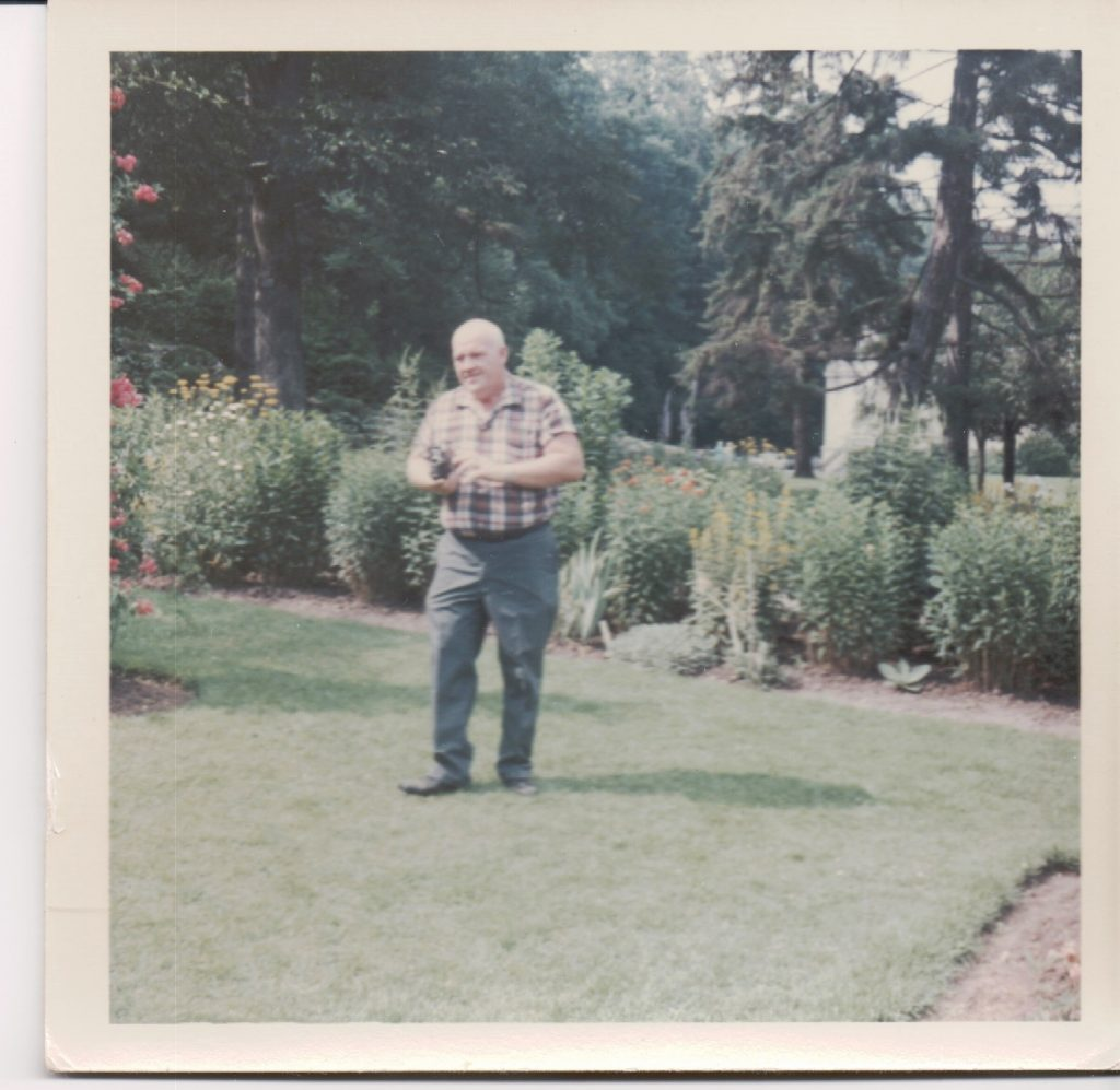 Color photo of a balding man wearing blue pants and a short sleeved plaid shirt. He's standing in what appears to be a garden.