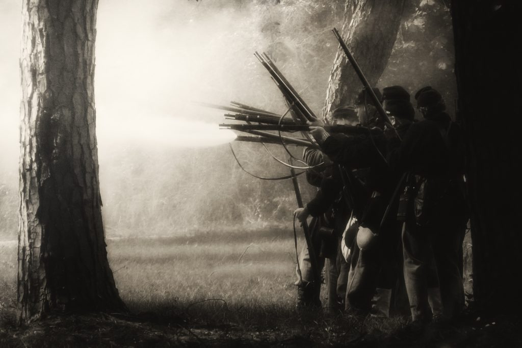 B&W of Civil War reenactors standing near trees and shooting rifles.