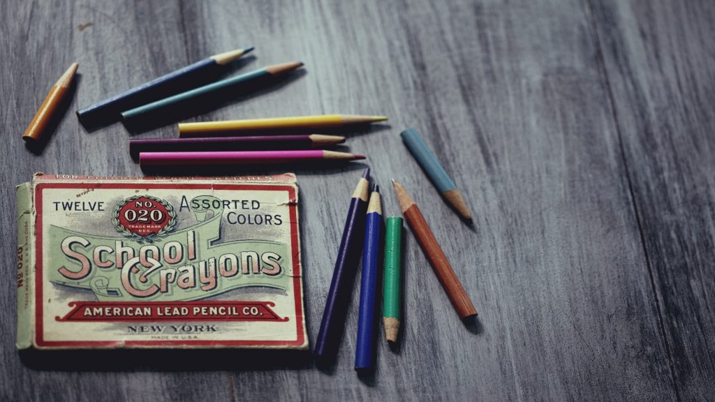 Color photo of a vintage box of school crayons with color pencils, all on a slate table.