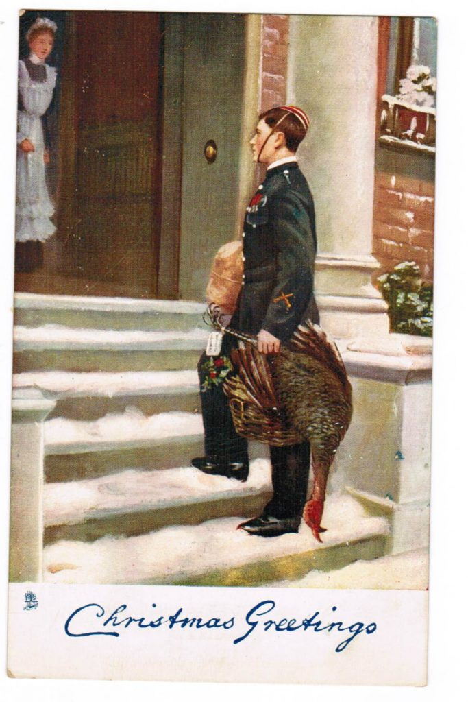 A young soldier on the steps of a home carrying a dead turkey in a basket. He has another parcel under his arm. His uniform is a dark green, and he has a red hat held on with a string around the chin. There is a maid at the door wearing a dark dress, a white apron, and a white hat. 'Christmas Greetings' is in a cursive font and in blue.