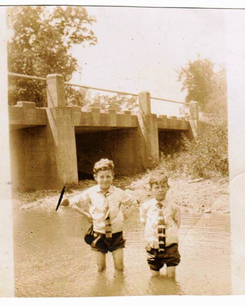 B&W photo of two boys standing in creek. Each boy is wearing a long sleeve white shirt, a dark tie, and dark pants rolled up to above their knees. Boy on left smiling, boy on right not.
