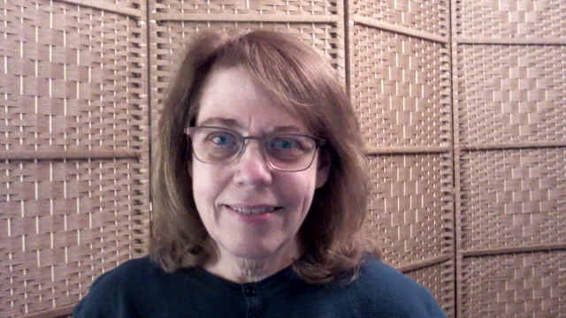 Color photo of woman with shoulder-length medium brown hair, wearing brown framed glasses, and a green shirt.