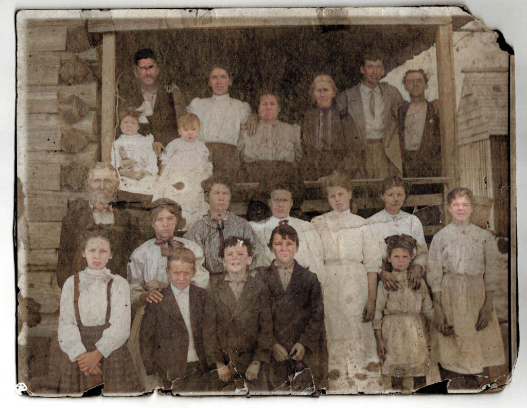 Colorized photo  of a large family with the Rainmaker -a man who was hired to come make it rain. Family is partly on a porch and partly in front of the porch. Three generations in this photo.