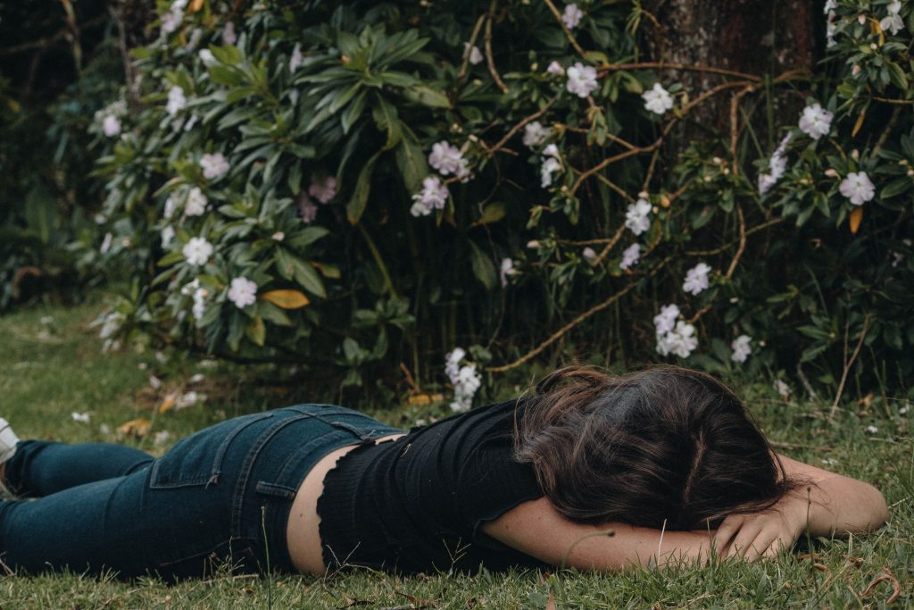 Color image of a woman with long brown hair in black shirt and jeans lying face down in the grass with face hidden.