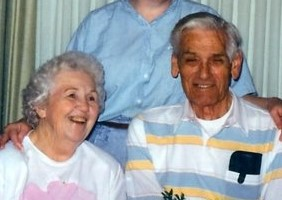 Color photo of an elderly couple, both smiling.  Wearing casual clothes.