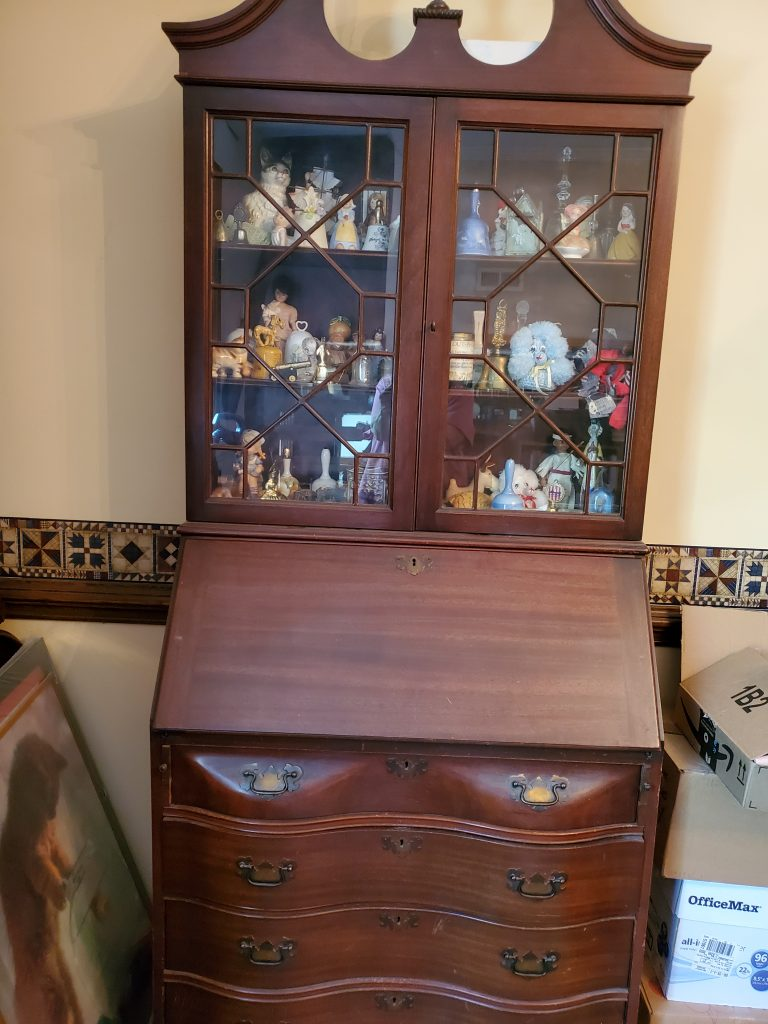 A tall piece of dark brown wooden furniture that is desk on the bottom and glass-doored showcase on the top.