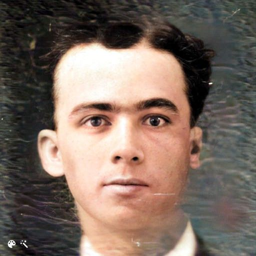 Close up of a clean-shaven young man and short, wavy, dark hair and dark eyes.