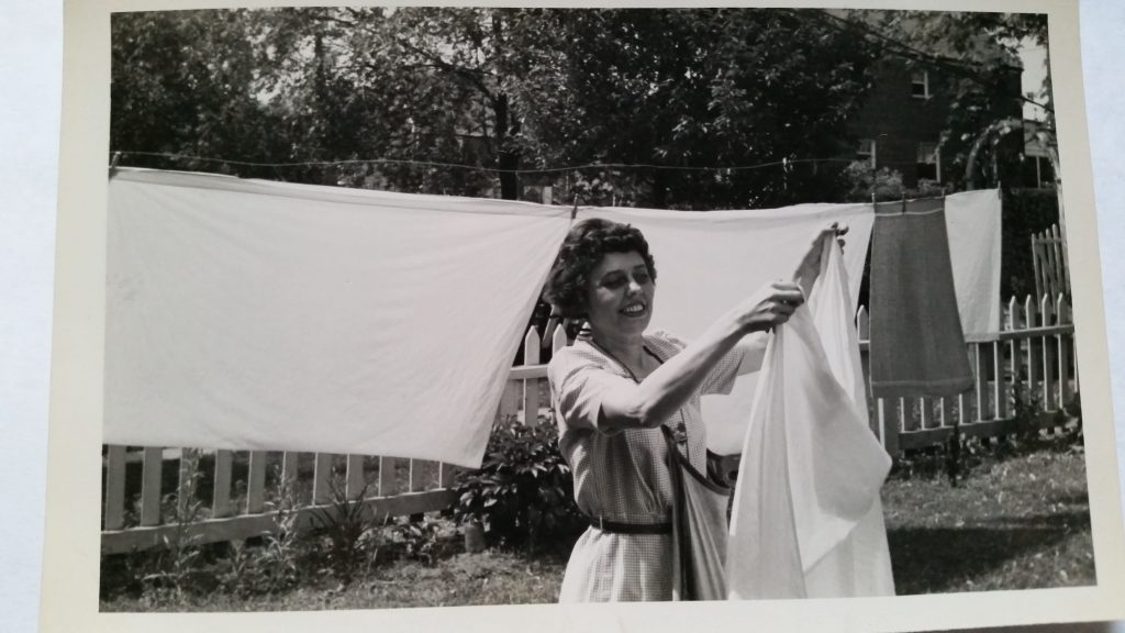 Black and white photo of a middle-aged woman with short dark hair hanging laundry on an outdoor clothes line