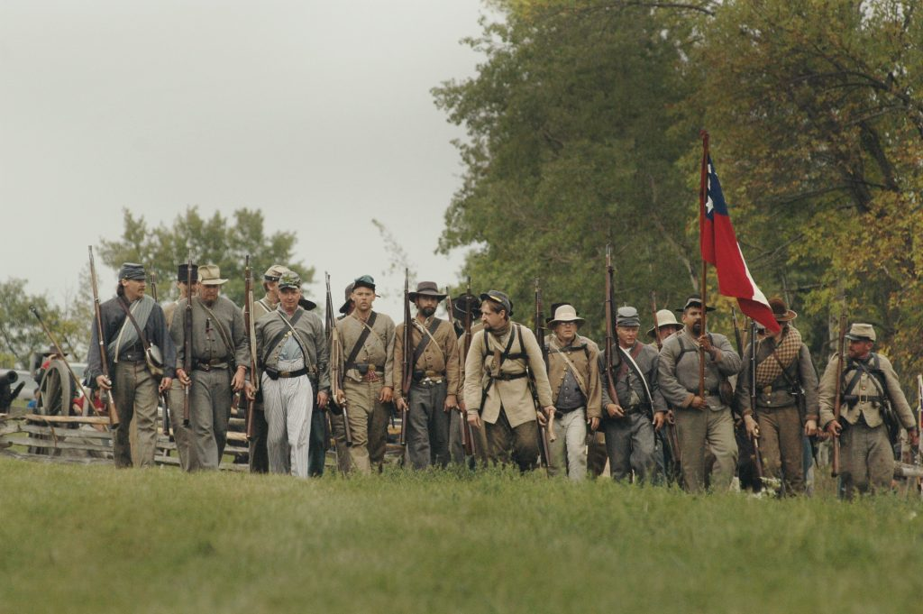 Color photo of Civil War reenactors walking in a row. All with rifles and clothes of the era, one man carrying the flag.