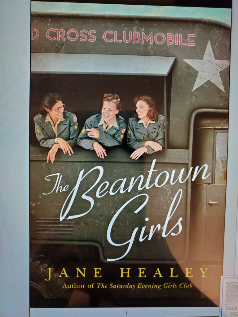 Photo of front The Beantown Girls book. Cover shows 3 young women leaning on the open window in the side of a large camouflage colored truck.