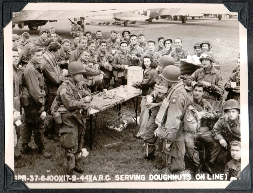 Black and white photo of young woman serving coffee and donuts to many soldiers on an airstrip during World War 2.