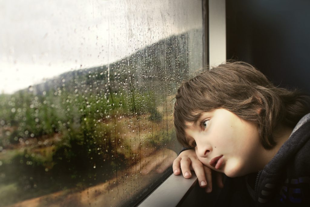 Young person with head leaning on window sill. Rain on the glass.