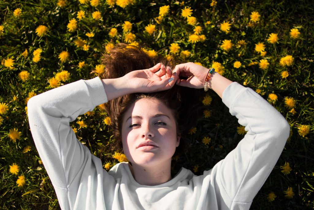 Young woman with dark hair laying in a field of dandelions